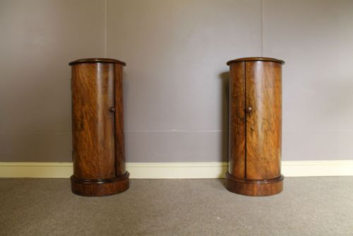 a pair of walnut cylindrical bedside cupboards
