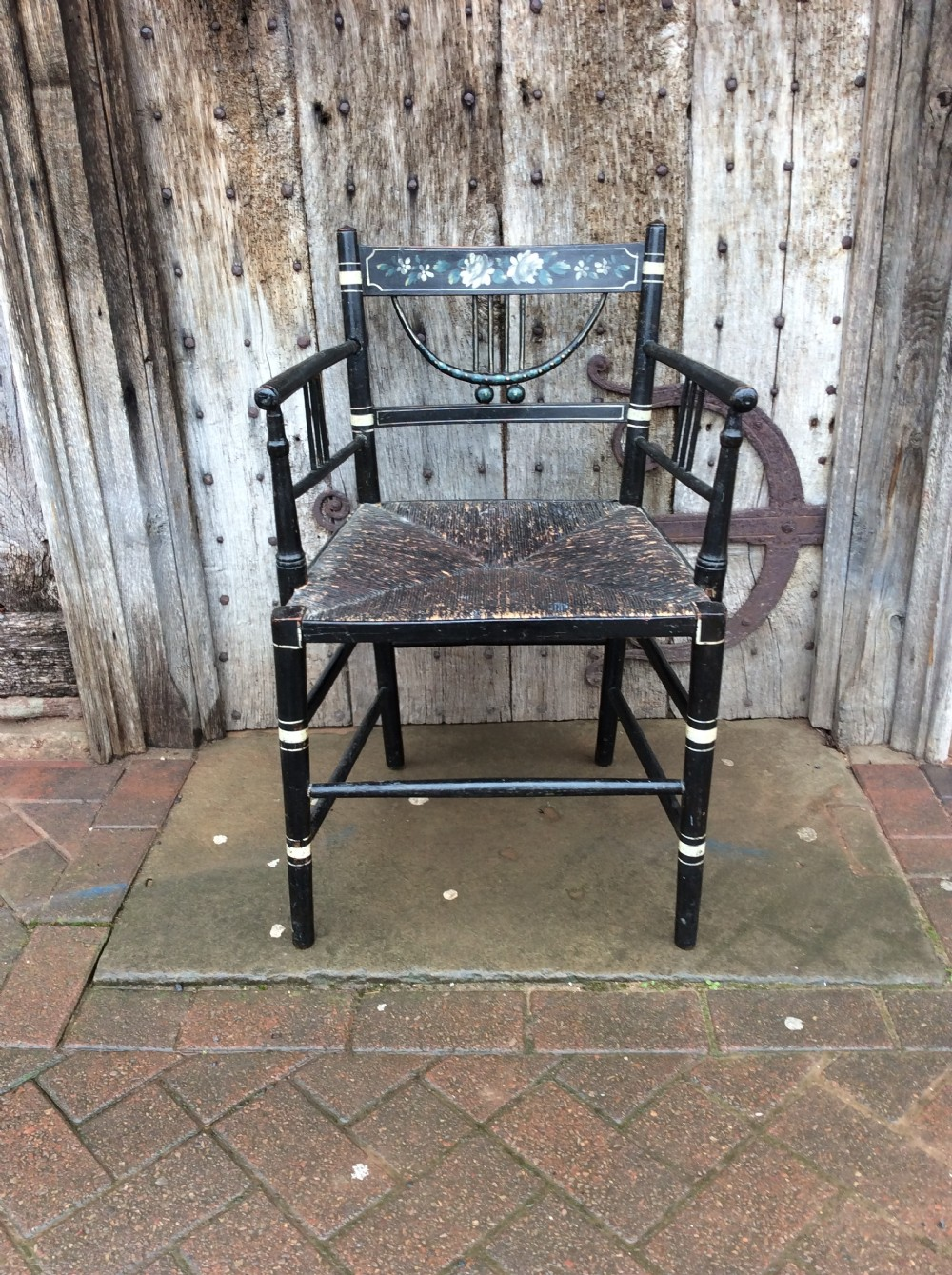 a regency ebonised and decorated rush seated chair